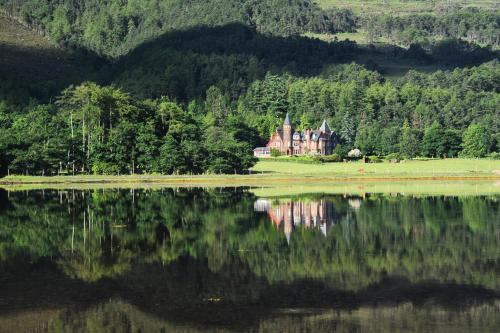 Torridon Hotel surrounded by forest and with Torridon Loch in the foreground